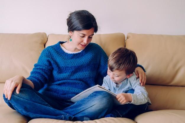 Kleiner junge hört eine geschichte aus einem buch mit mama. lebensstil mit kindern im haus. kleines kind zu hause geerdet. junge mutter liest ihrem kind die hausaufgaben ohne schulzeit vor. Premium Fotos