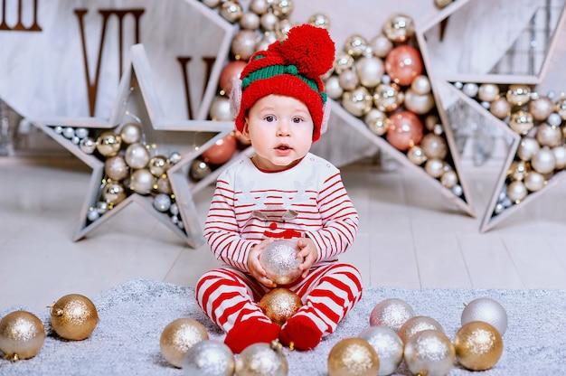Kleiner junge im elfenhut, der auf ein weihnachten wartet, das baumdekoration hält, Premium Fotos