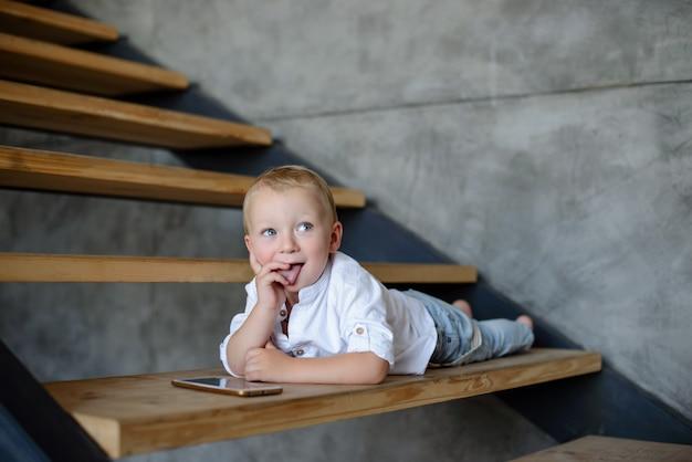 Kleiner junge im weißen hemd und in den jeans Premium Fotos