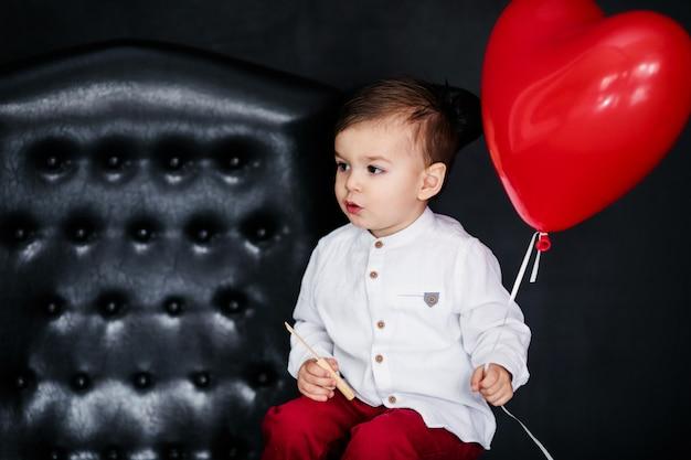 Kleiner junge im weißen hemd und in roter hose, die auf dem lehnsessel mit rotem herzballon am valentinstag sitzen Premium Fotos