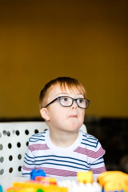 Kleiner junge in den gläsern mit der syndromdämmerung, die mit bunten ziegelsteinen spielt Premium Fotos