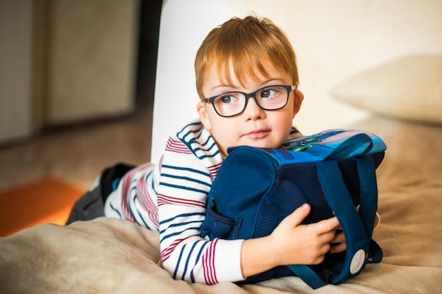 Kleiner junge in den gläsern mit der syndromdämmerung, die mit rucksack spielt Premium Fotos