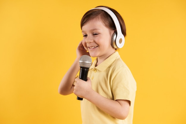 Kleiner junge in den kopfhörern singt am karaoke. Premium Fotos