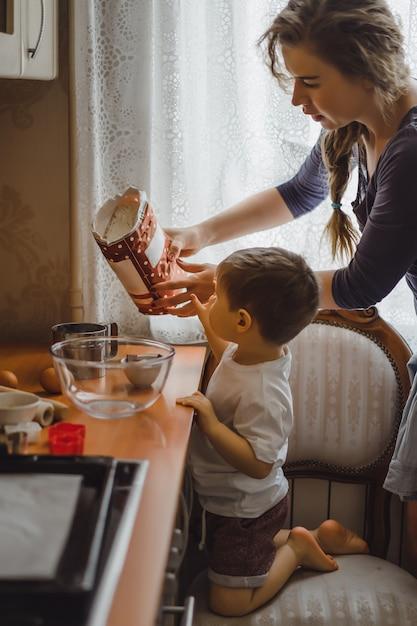Kleiner junge in der küche hilft mama beim kochen. das