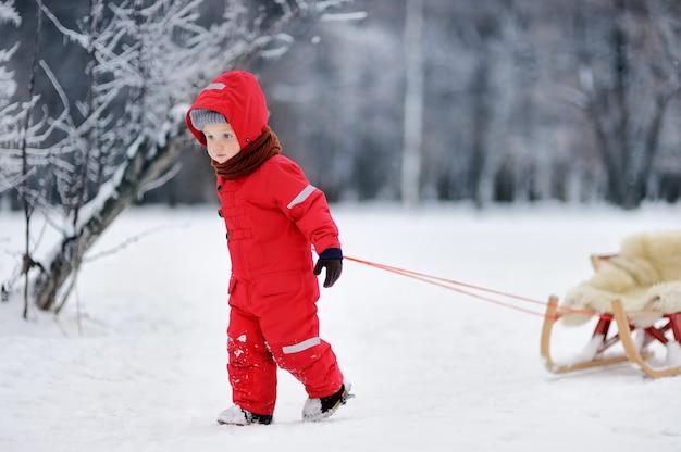 Kleiner junge in roter winterkleidung mit rodel. aktivurlaub im freien mit kindern im winter Premium Fotos