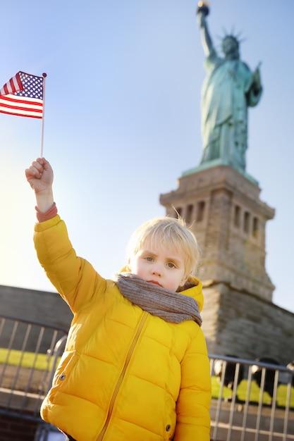 Kleiner junge mit amerikanischer flagge auf dem hintergrund des freiheitsstatuen in der gleichen haltung. reisen sie mit kindern. Premium Fotos
