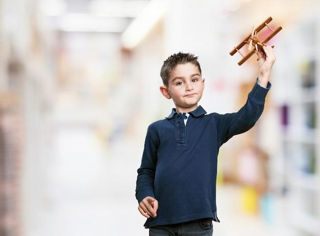 Kleiner junge mit einer holz-flugzeug spielen Kostenlose Fotos