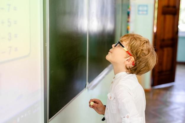 Kleiner junge mit großen schwarzen gläsern und dem weißen hemd, die nahe schultafel mit einem stück kreide intelligentes denkendes gesicht machend steht Premium Fotos