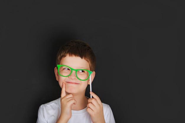 Kleiner junge mit grünen gläsern in der nähe von tafel. Premium Fotos