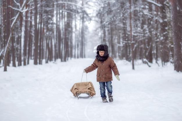 Kleiner junge mit schlitten im winterwald Premium Fotos