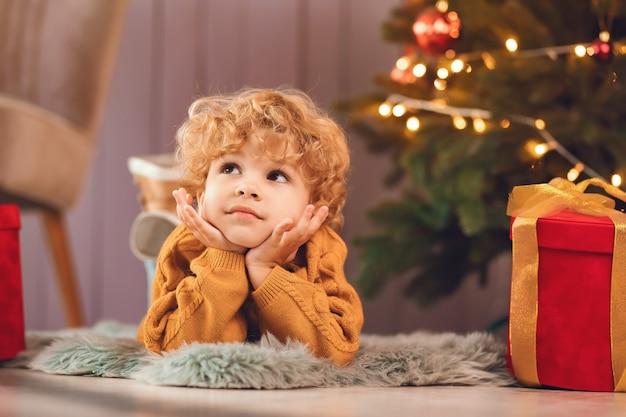 Kleiner junge nahe weihnachtsbaum in einer braunen strickjacke Kostenlose Fotos