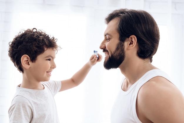 Kleiner junge putzt zähne des bärtigen mannes mit zahnbürste. Premium Fotos