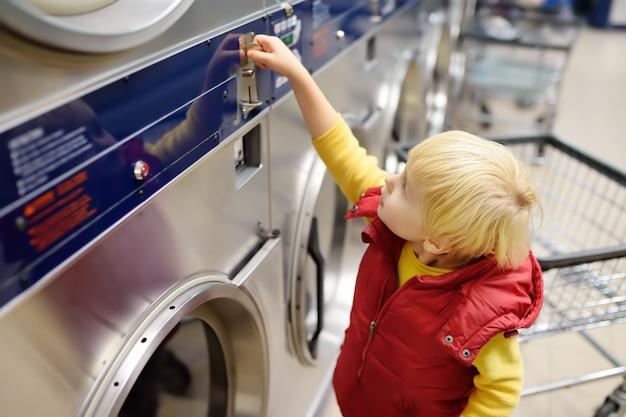 Kleiner junge setzt münze in die wäscherei des trockners in der öffentlichkeit ein Premium Fotos