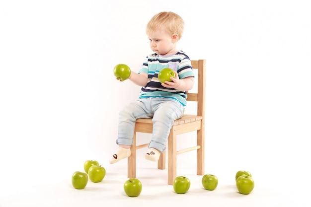 Kleiner junge sitzt auf einem stuhl, umgeben von äpfeln Premium Fotos