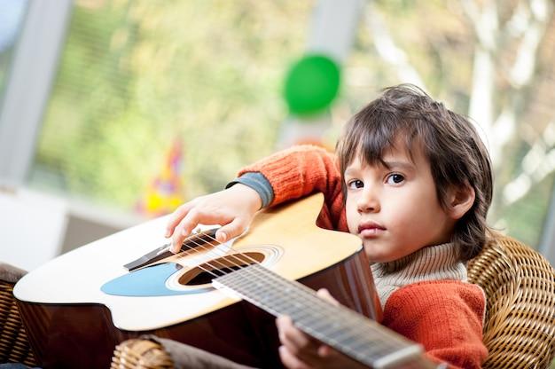 Kleiner junge spielt auf der gitarre Premium Fotos