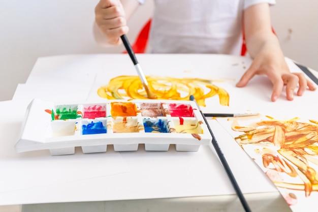 Kleiner junge spielt mit hausgemachten farben Premium Fotos