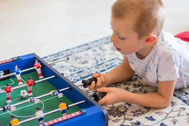 Kleiner junge spielt mit tischfußball Premium Fotos