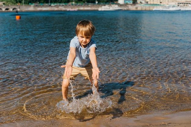 Kleiner junge spielt mit wasser am ufer Kostenlose Fotos