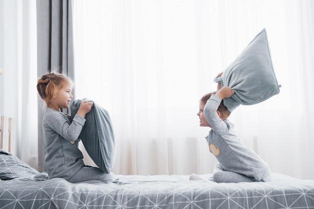 Kleiner junge und kleines mädchen inszenierten eine kissenschlacht auf dem bett im schlafzimmer. freche kinder schlagen sich gegenseitig auf die kissen. sie mögen diese art von spiel Premium Fotos