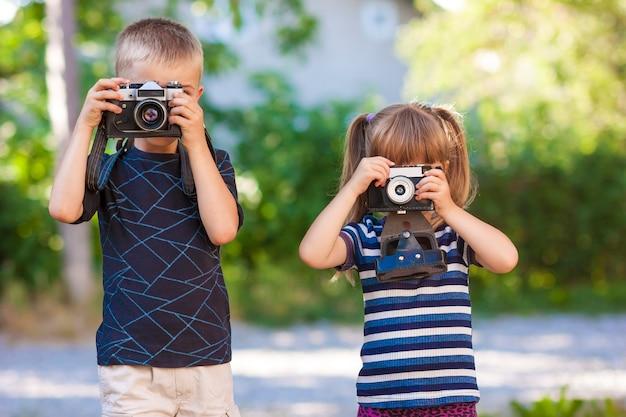 Kleiner junge und mädchen lernen, wie man eine fotokamera benutzt Premium Fotos