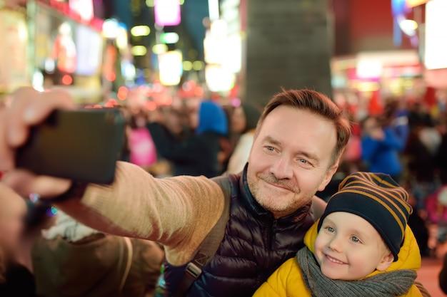 Kleiner junge und sein vater, die selfie auf times square am abend, im stadtzentrum gelegenes manhattan nimmt. Premium Fotos