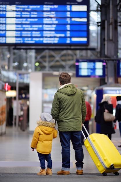 Kleiner junge und sein vater im internationalen flughafen oder auf der bahnhofsplattform, die auf informationsanzeige schaut Premium Fotos