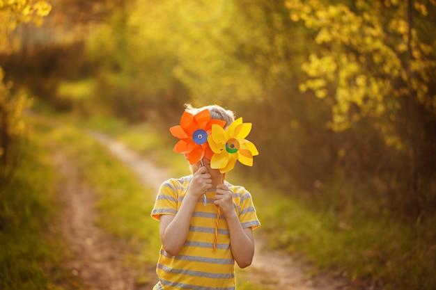 Kleiner junge versteckt sich hinter den gelben und orange feuerrädern auf grünem waldhintergrund am sonnigen tag. Premium Fotos