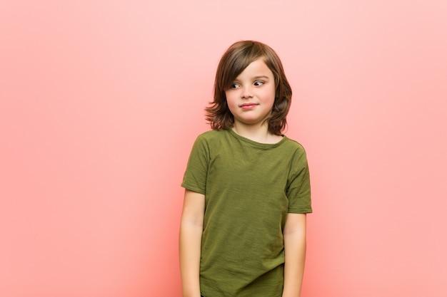 Kleiner junge zuckt verwirrt mit den schultern und den offenen augen. Premium Fotos