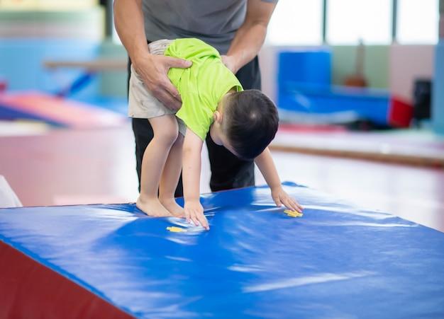 Kleiner kleinkindjunge, der an der innengymnastikübung ausarbeitet Premium Fotos