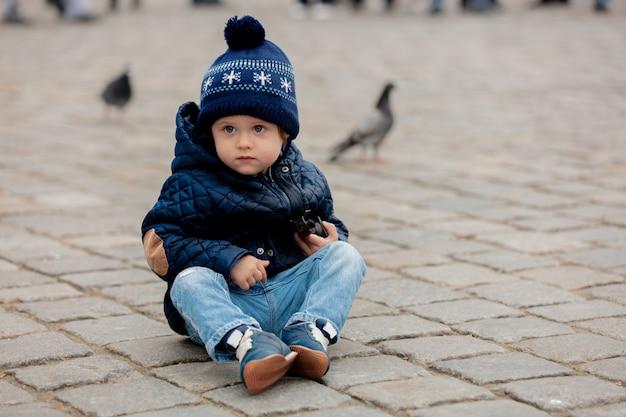 Kleiner kleinkindjunge, der auf pflastersteinen im stadtplatz sitzt Premium Fotos
