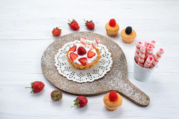 Kleiner köstlicher kuchen mit sahne und geschnittenen roten frischen erdbeerkuchen auf weißen, kuchenbeeren-süßen backfrüchten Kostenlose Fotos