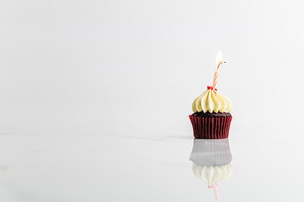 Kleiner kuchen mit kerze geburtstagsfeier auf weißem hintergrund, jahrestagskonzept Premium Fotos