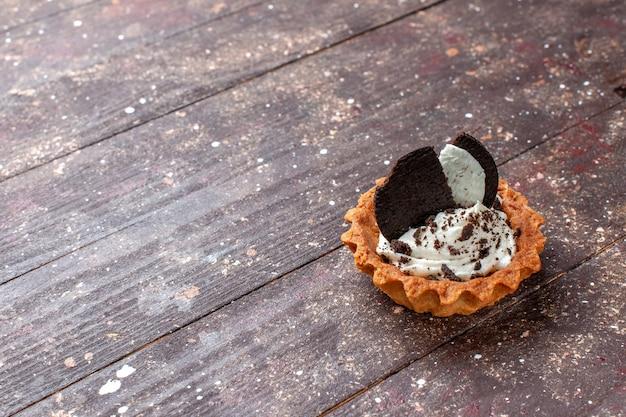 Kleiner kuchen mit sahne und schokoladenplätzchen lokalisiert auf hölzernem braunem schreibtisch, kuchenbiskuit-backfarbe Kostenlose Fotos