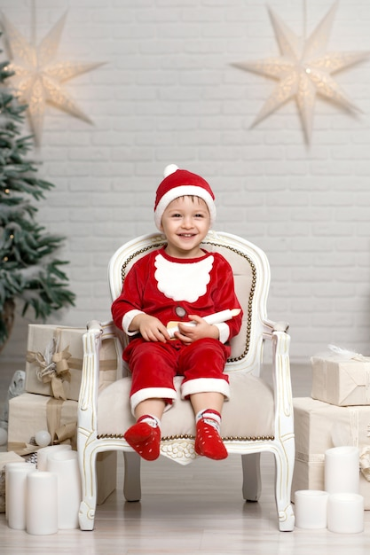 Kleiner lächelnder junge in weihnachtsmann-kostüm sitzt auf lehnsessel nahe weihnachtsbaum und hält weiße kerze in den händen Premium Fotos