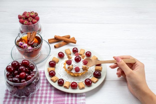 Kleiner leckerer kuchen mit himbeerkirschen und kleinen keksen tee zimt auf hellem schreibtisch, obst beeren sahne tee Kostenlose Fotos