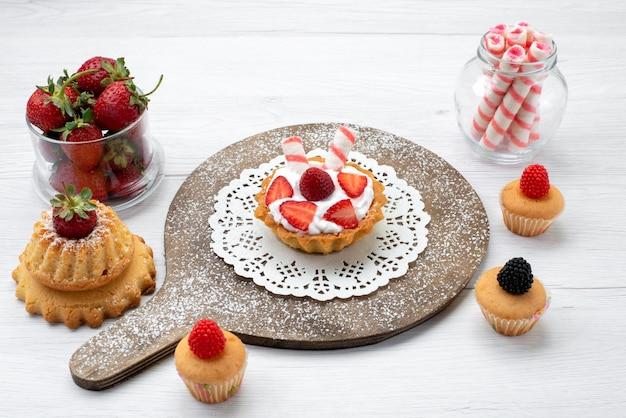 Kleiner leckerer kuchen mit sahne und geschnittenen erdbeerkuchen auf weißem boden kuchen beere süß backen obst backen Kostenlose Fotos