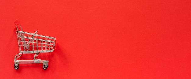 Kleiner leerer einkaufswagenwagen auf rotem hintergrund. Premium Fotos