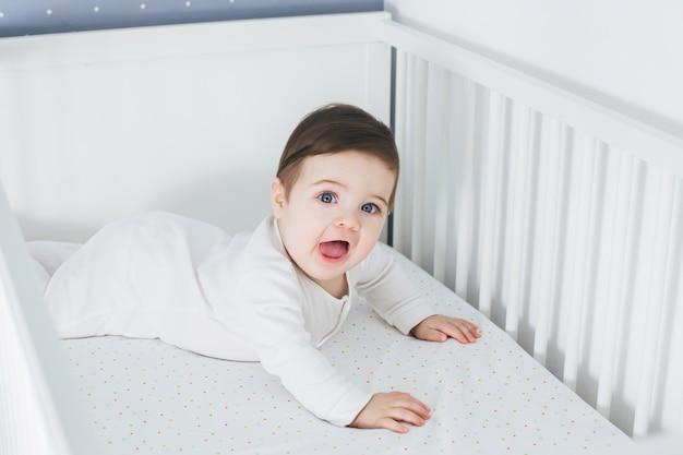 Kleiner lustiger junge, der im babybett liegt und lacht Premium Fotos