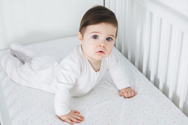 Kleiner lustiger junge, der im babybett liegt Premium Fotos