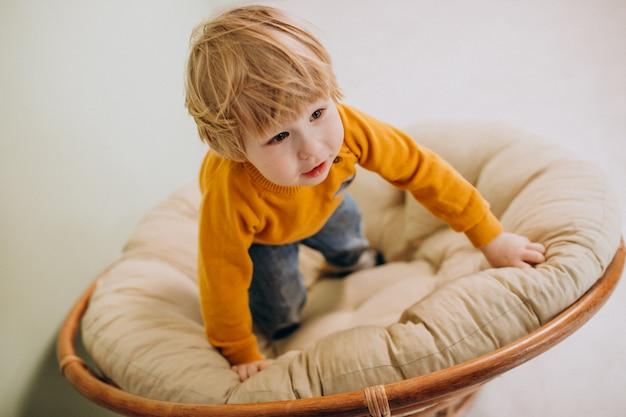 Kleiner netter junge, der in einem stuhl sitzt Kostenlose Fotos