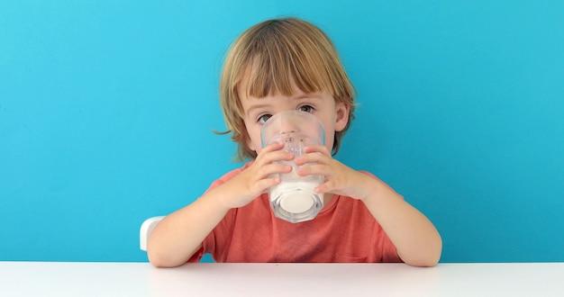 Kleiner netter junge trinkt milch Premium Fotos