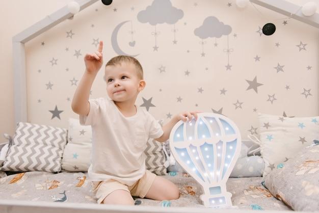 Kleiner niedlicher kleiner junge, der im kinderzimmer in einem hölzernen betthaus mit nachtlichtern in der form eines ballons sitzt Premium Fotos