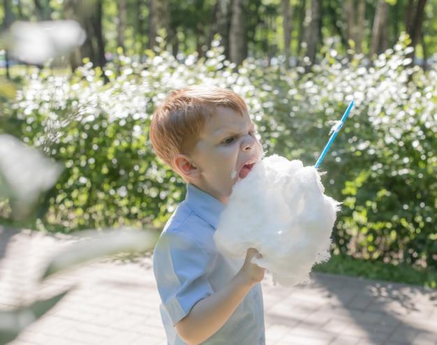 Kleiner rothaariger junge mit zuckerwatte Premium Fotos