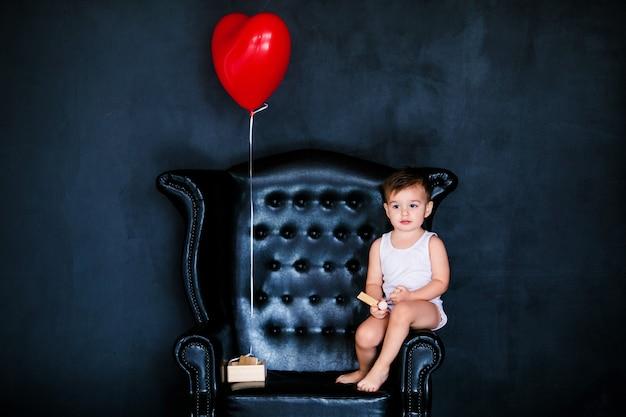 Kleiner säuglingsjunge 2 jahre alt im weißen t-shirt, das auf dem lehnsessel mit rotem herzballon sitzt Premium Fotos