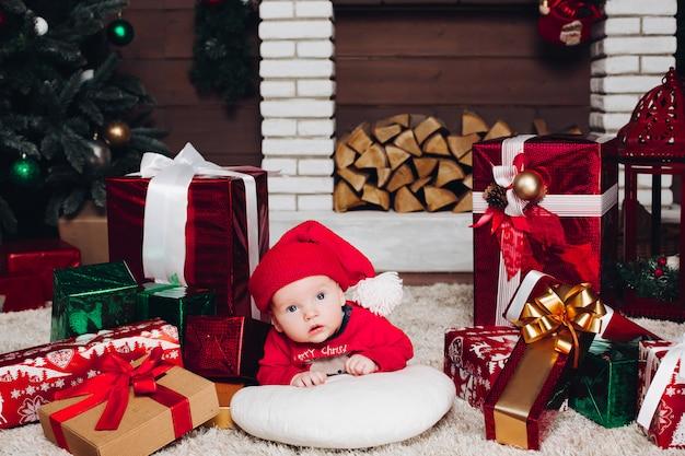 Kleiner sankt-junge, der auf fußboden in verziertem haus mit weihnachtsgeschenken liegt Premium Fotos