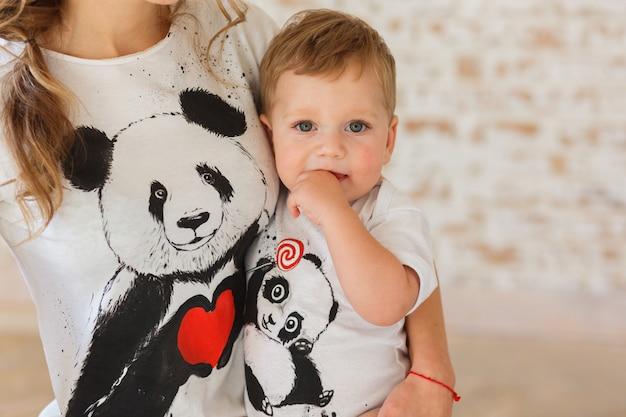 Kleiner sohn auf mutters händen. familylook von t-shirts mit pandas Kostenlose Fotos
