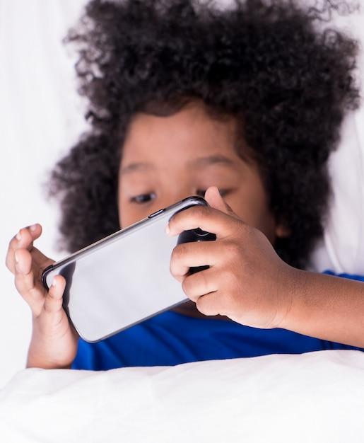 Kleines afrikanisches kind spielt mit smartphone auf bett Premium Fotos