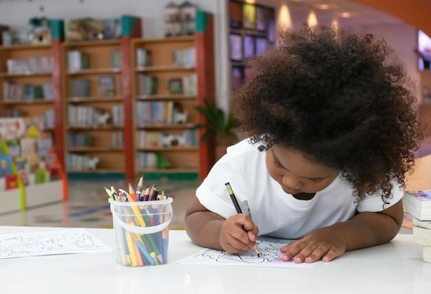 Kleines afrikanisches mädchen, das mit glück malt und zeichnet. Premium Fotos