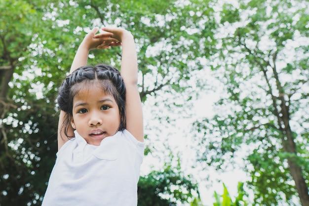 Kleines asiatisches kindermädchen, das im allgemeinen park yoga tut. Premium Fotos