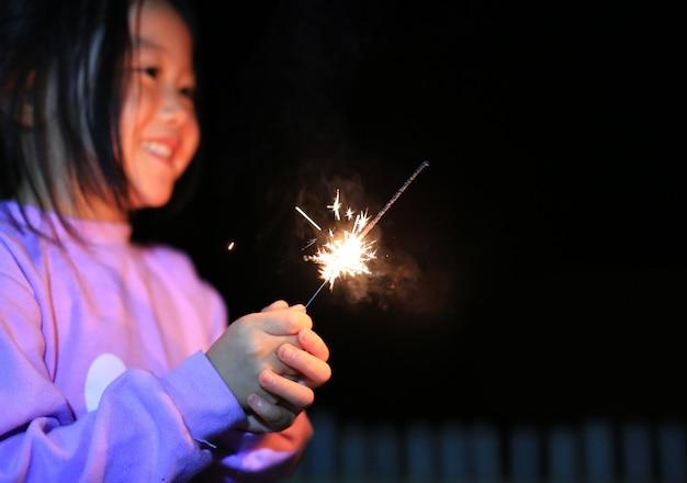 Kleines asiatisches kindermädchen genießen, kracher zu spielen Premium Fotos